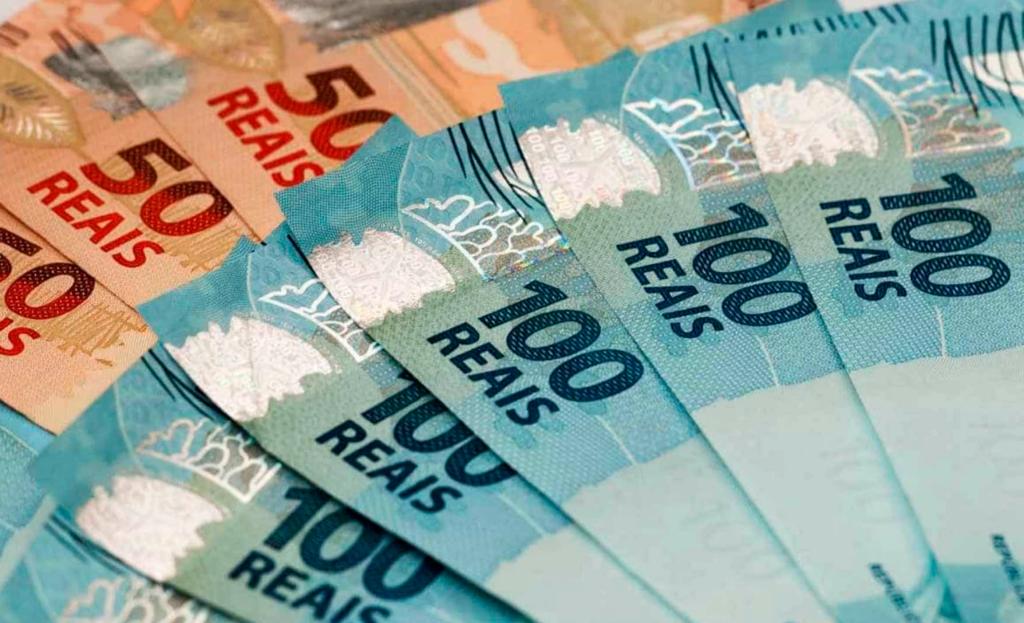 Amontoado de notas de 100 e 50 reais, simbolizando a mudança na tributação do Brasil