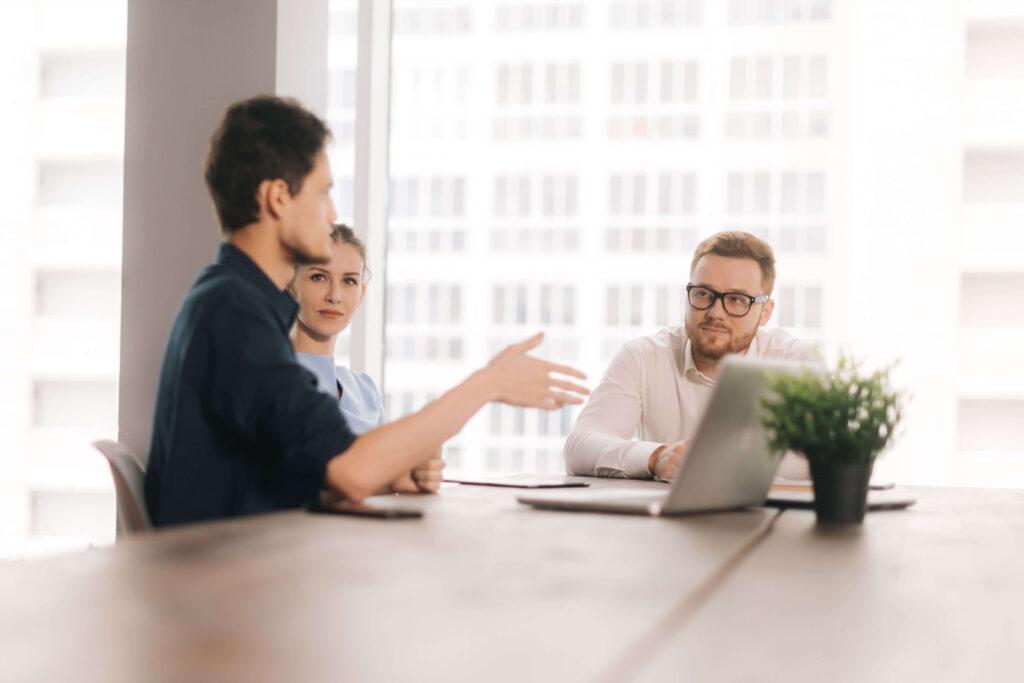 Dois homens e uma mulher, sócios, em reunião, sentados à mesa debatendo o negócio